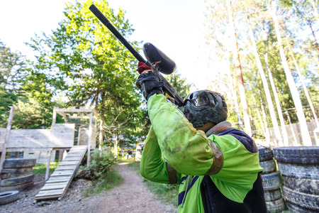 Cool extreme sportsman shooting from paintball marker