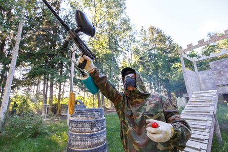 Boy with paint grenade shooting from paintball marker