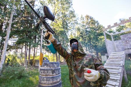 Chłopiec z farba granat strzelanie z paintball marker
