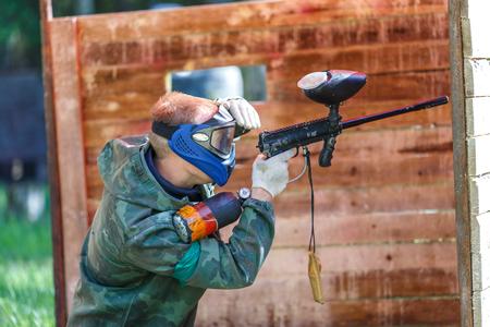 Paintball graczem w niebieskim kasku strzelanie z pistoletu do malowania