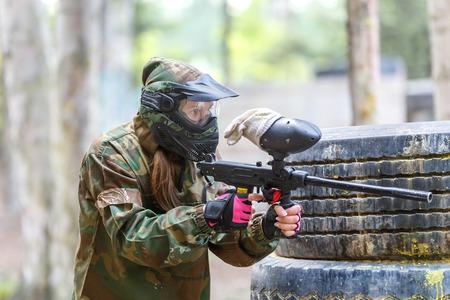 Прохладный девушка с краской пистолет игры в пейнтбол игры