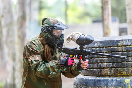 Cool girl with paint gun playing paintball game Фото со стока