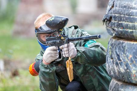 Прохладный пейнтбольный игрок стрельбы из маркера на открытом воздухе