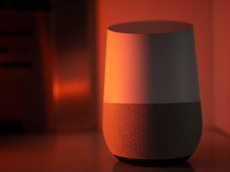 Smart home speaker assistant device in moody coloured LED lighting - Orange Stock Photo