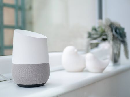 Smart home assistant speaker on windowsill in daylight in home setting