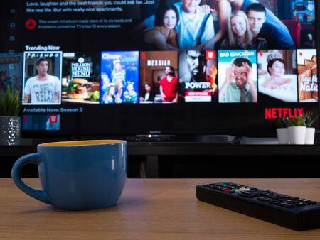 Großbritannien, Januar 2020: Netflix-Trend-Menü wird auf dem Fernseher in der häuslichen Umgebung mit Tasse angezeigt