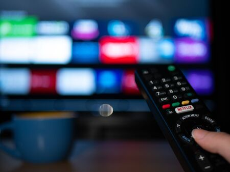 UK, Jan 2020: Netflix remote control with android apps on smart TV screen in home setting Editorial
