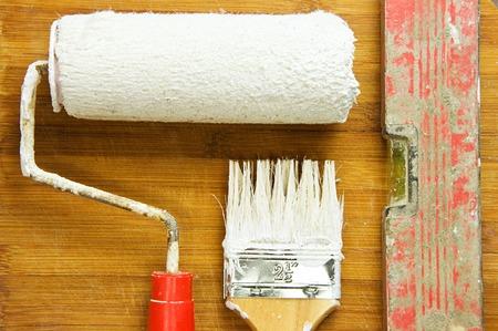 pintor de casas: Herramientas de pintura manchadas con pintura blanca sobre el fondo de tablas de madera