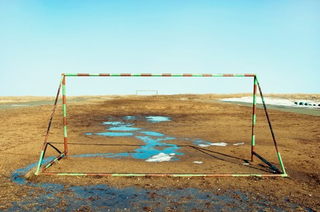weather beaten: Football goal on the field with puddles