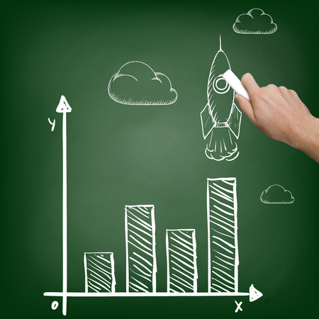 chalk board: Businessman with chalk in hand draws a graph