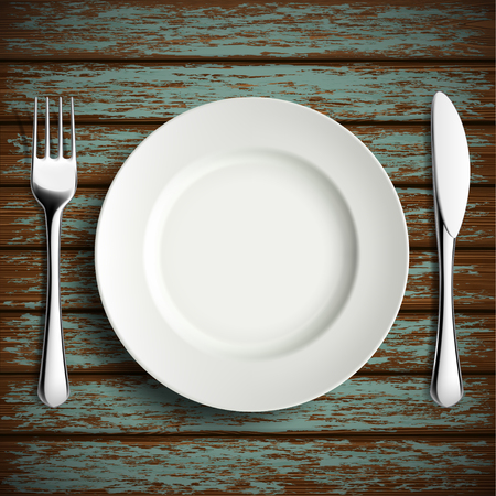 settings: Porcelain plate, fork and knife on a wooden table.