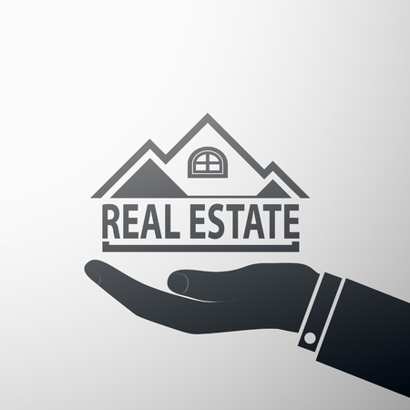 realestate: Human hand holding a house. The emblem of the real estate.