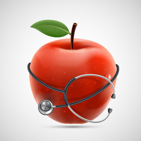 Medical equipment stethoscope around a red apple.
