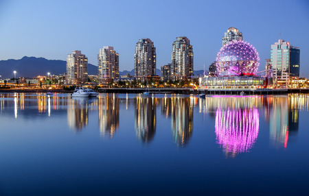 A beautiful clear summer night in Vancouver, BC features a pink glowing Science World  with reflections on the water at dusk