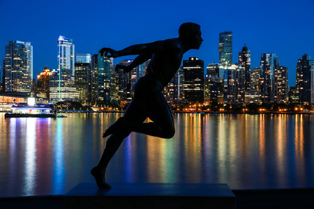 The Olympian runner Harry Jerome statue is silhouetted with Vancouver in the background, reflecting the night lights on the water