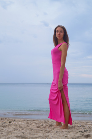 pink dress: Beautiful girl in pink dress standing near sea and smilling.