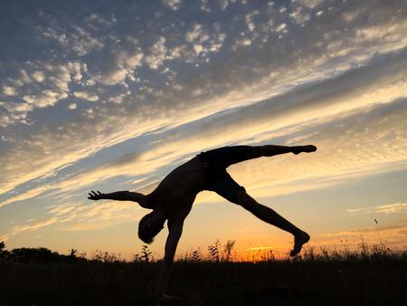 balancing act: Acrobat at sunset. Handstand. Stock Photo