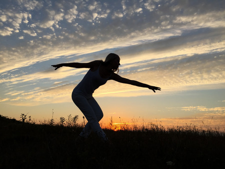 sexual position: Girl dancing at sunset.