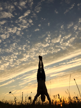 balancing act: Acrobat standing in her hands at sunset. Handstand. Stock Photo