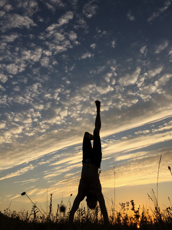 handstand: Acrobat standing in her hands at sunset. Handstand. Stock Photo