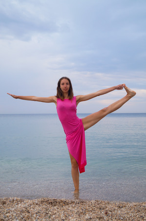 slander: Action near sea. Beautiful girl standing in yoga pose in red dress.