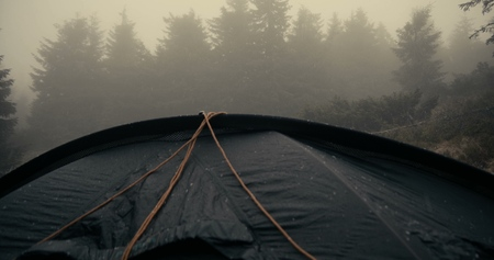 Spherical touristic tent is under heavy rain droplets in Carpathians
