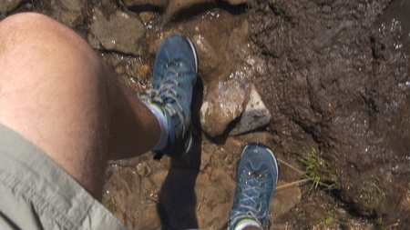 Hairy male legs in snickers going in a mountain rill with stones 写真素材