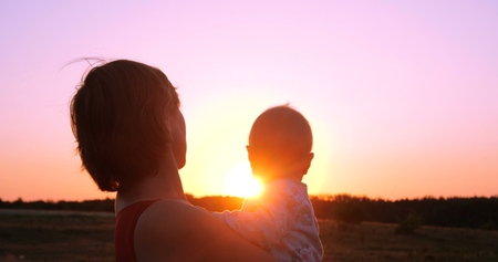 Cheery woman with a child in hands looking at splendid sunset outdoors 免版税图像
