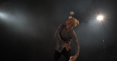 The juggler in the black studio make trick with four balls.