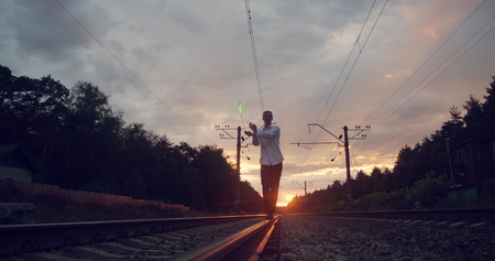 Gentalman artist makes trick on the railway at sunset. 免版税图像