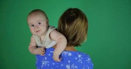 Grandmother and her baby in studio on green screen.