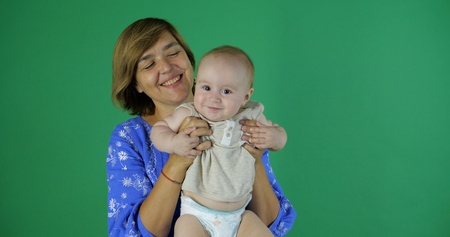 Cute play of aged woman with 1 year child in studio on the green screen. 写真素材