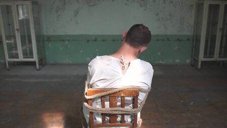 One kook man sitting being tied to a chair in shabby room Banco de Imagens
