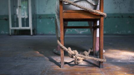 One wack man sitting tied to an old blue chair in shabby room