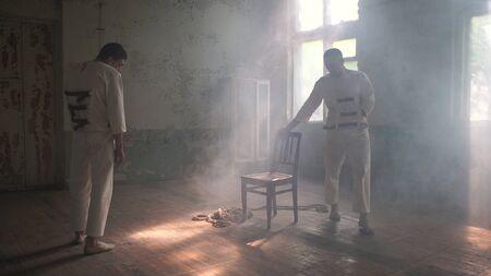 Dos amigos psicópatas dando vueltas a la silla apoyándose mutuamente en la casa mental