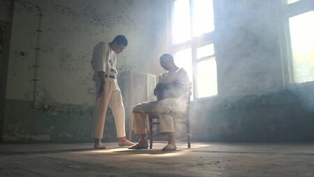 Two psycho men helping and moving on each other in mental hospital