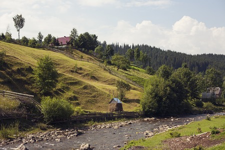 Small settlement in the mountains. Houses outbuildings and fields. Rural nature Mountain river road fence