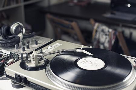 soundtrack: DJ mixer with a vinyl record, close up.