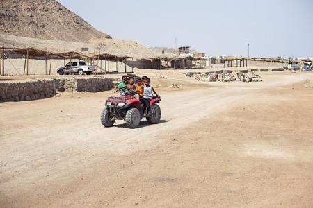 affability: Egypt Sharm el sheikh - august 2016: egyptians children ride on a quad bike. Desert