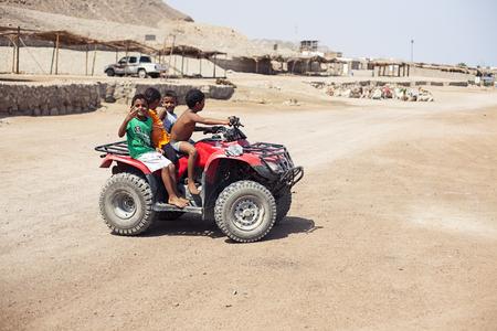 Egypt Sharm el sheikh - august 2016: egyptians children ride on a quad bike. Desert