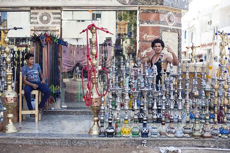 affability: Egypt Sharm el sheikh - august 2016: hookah shop bazaar sell with friendly dealer, friendliness gestures Editorial