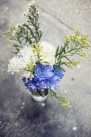 A simple bouquet of flowers in a vase on the pavement Stock Photo