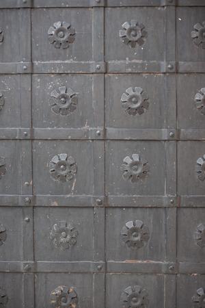 door knob: A large massive ancient metal wrought-iron black door Stock Photo