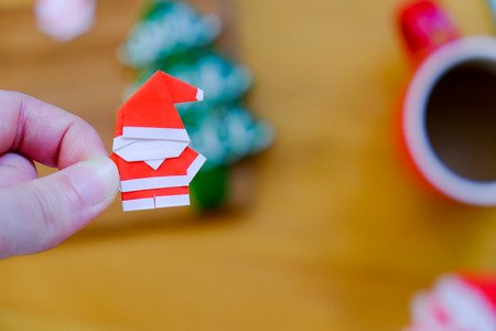 Paper origami Santa Claus on hand with blurred background