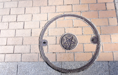 sewer: Sewer manhole cover in brick street Stock Photo