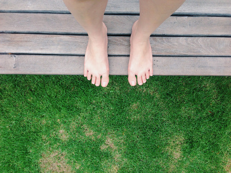 View of bare feet on green grass in the garden
