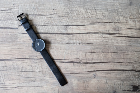 wooden clock: Minimal black watch on artificial wood background