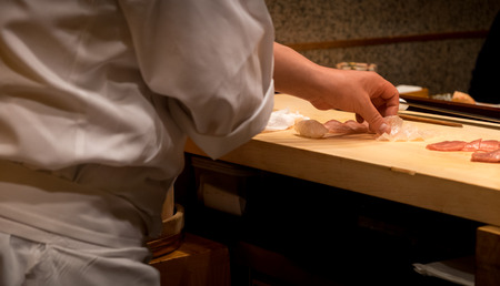 Japanese chef slicing fresh raw fish for sushi