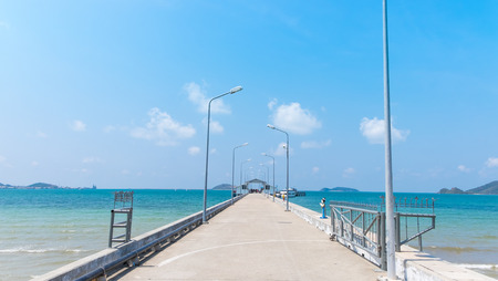 Walkway to pier among blue sea and clear sky