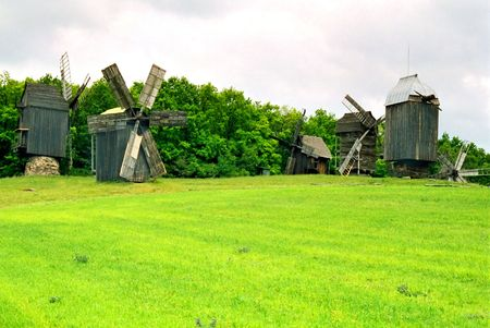 Wooden mills on the field of green grass. photo